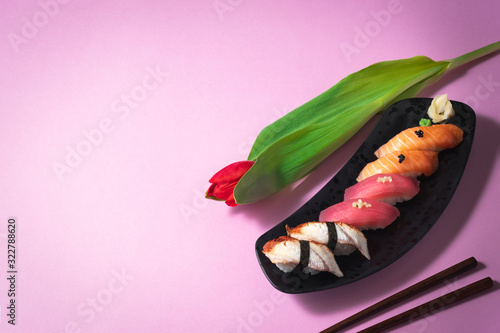 Sushi set with flower on pink background. Salmon, tuna and eel sashimi nigiri. Valentines Day (14 February), Mother's day, Woman's day (8 March), date or spring concept. Japanese food. Copy space