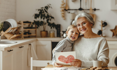 happy family grandson child congratulates grandmother on holiday and gives card