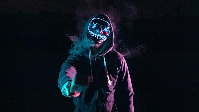 Chico con una máscara de luces con humo y un bate