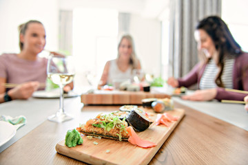 Focus on sushi with a Group of attractive mature people eating sushi at home on the back