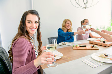 Group of attractive mature people eating sushi at home