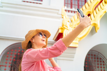 Tourist caucasian foreign backpack  women take selfie photo by smartphone wear sunglass in buddhism temple