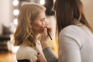 Makeup artist work in her beauty studio. Portrait of Woman applying by professional make up master. Beautiful make up artist start making a makeup for blond hair model