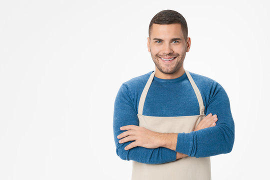 Young handsome shopkeeper man wearing apron standing over isolated white background