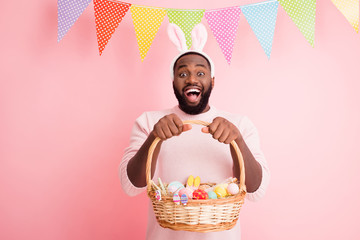 Photo of funny dark skin guy came easter party hold festive basket ginger bread painted eggs cookies wear sweater bunny ears colorful flags hang pastel pink color background