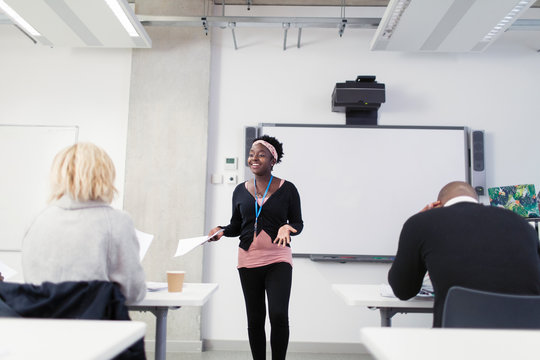 Smiling happy female community college instructor leading lesson
