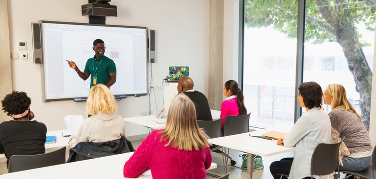 Community college students watching instructor leading lesson
