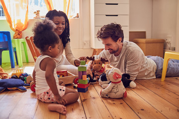 Young family playing with toys on floor