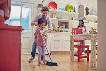 Father and daughter sweeping kitchen floor with broom