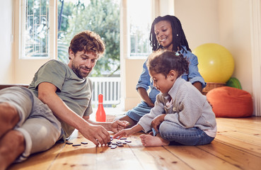 Young family playing with dominos on floor