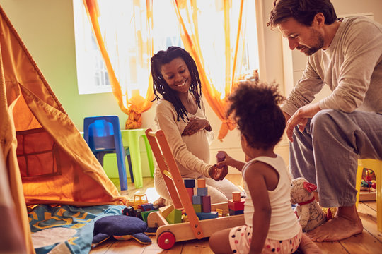 Pregnant young family playing with toys
