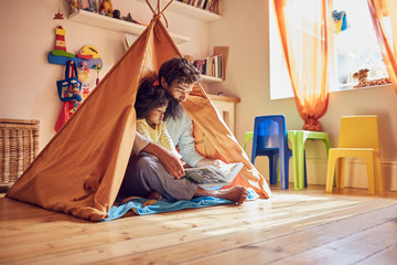 Father and toddler daughter reading book in teepee