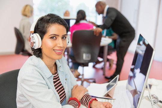 Portrait confident woman with headphones at computer