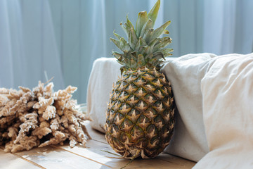 Close up picture of pineapple in light boho interior