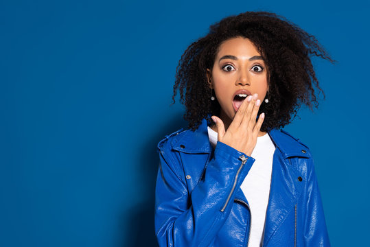 shocked african american woman coveting mouth with hand on blue background