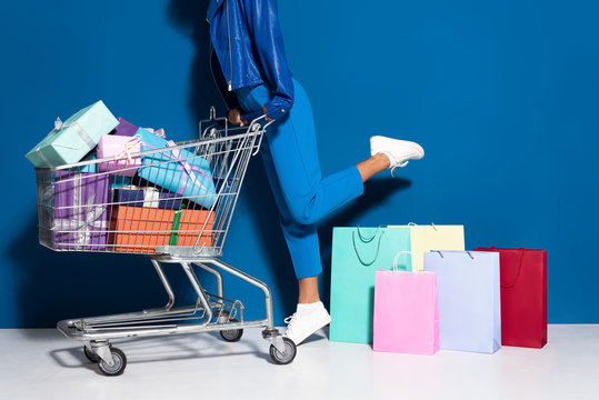cropped view of african american woman with shopping cart full of gifts near shopping bags on blue background