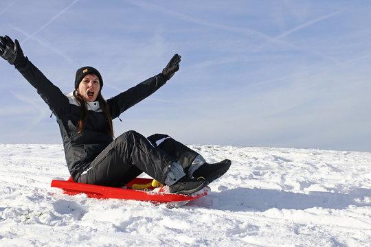 Eine junge Frau hat im Winter Spaß beim Schlittenfahren