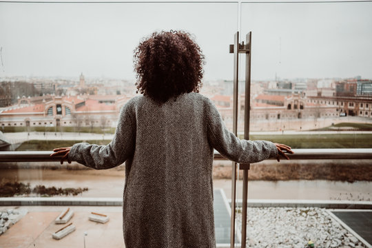 .Beautiful African American woman looking backwards out the window of a tall building overlooking the city of Madrid. Relaxed and carefree. Lifestyle