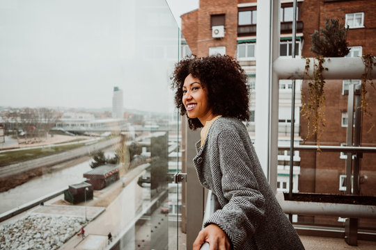 .Beautiful African American woman looking out the window of a tall building overlooking the city of Madrid. Relaxed and carefree. Lifestyle