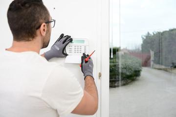 Obraz handsome man worker installing alarm technology insurance in home for burglar prevention - fototapety do salonu