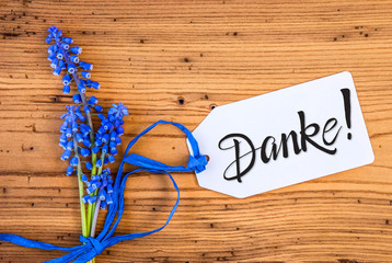 Label With German Calligraphy Danke Means Thank You. Blue Spring Hyacinth Flower On Rustic Wooden Background.