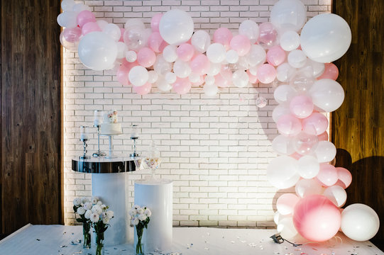 Photo-wall, wedding decoration space or place from white and pink balloons and white brick wall near table with a wedding cake, candles and flowers.