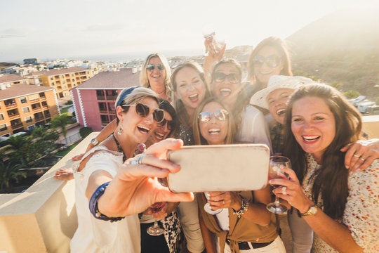 Group of happy and cheerful young women have fun in party together outdoor taking selfie picture with phone - people celebrate with wine and toasting in friendship - beautiful caucasian females laugh