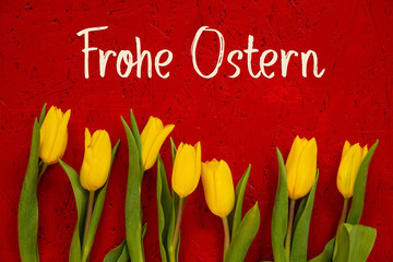 Red Wooden Background With German Text Frohe Ostern Means Happy Easter. Yellow Tulip Flowers In Spring Season
