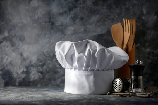White cook hat on desk and kitchen interior.Free space for your decoration.