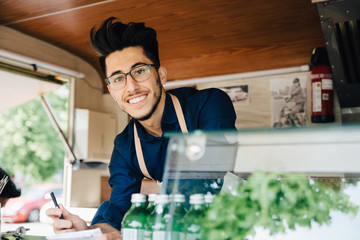 Portrait of happy male owner with pen standing in food truck