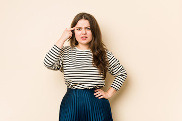 Young curvy woman showing a disappointment gesture with forefinger.