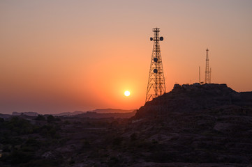 Telecommunication towers on hill in remote control area aganist sunset sky
