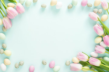Colored Easter candy eggs and pink tulips on turquoise background. Easter frame.