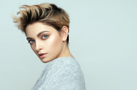 Portrait of sexy young woman with short hair isolated on gray background