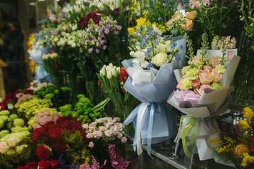 Different varieties fresh spring flowers in refrigerator room for flowers. Beautiful flowers in cold room with air conditioning. Bouquets on shelf, florist business in refrigerator for flowers. Tulinp