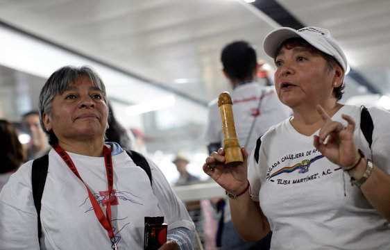 Members of an organization explain how to wear a condom during an event organized by AIDS Healthcare Foundation for the International Condom Day, at a metro station in Mexico City