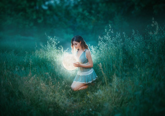 red haired witch. woman in blue green mint color short sexy dress, holds glow shining moon globe lamp. Casual fashion wear. Elf princess. Power of nature miracle. bright summer forest. Ball gold light