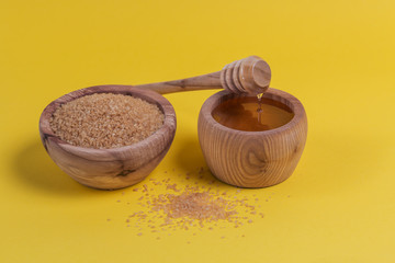 Brown sugar heap and honey in wooden bowl on yellow table
