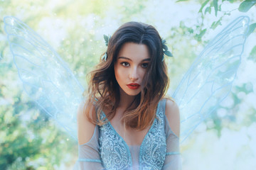 Fantasy closeup portrait attractive woman in image young fairy. carnival Costume blue dress transparent wings. face tender red makeup. Wavy Brunette hair Flutter fly in wind. Green nature backdrop
