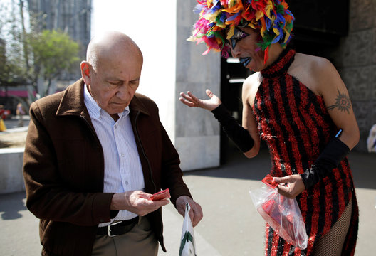 Polo Gomez, also known as drag queen Yolanda la del Rio, from organization Condomovil A.C., gives out a free condom to a man during an event organized by AIDS Healthcare Foundation for the International Condom Day, in Mexico City
