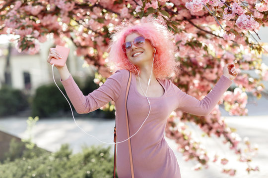 Happy woman with curly pink hair and sunglasses near the blossoming spring tree listening music on smartphone.