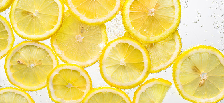 Slices of lemon in water with air bubbles on white background.