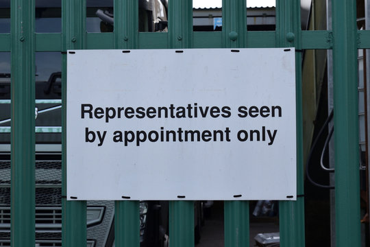 White Plastic Sign on Steel Fence 'Representatives Seen By Appointment Only'