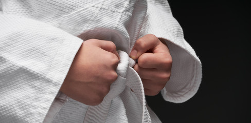 hands closeup - teenager dressed in martial arts clothing posing on a dark gray background, a sports concept