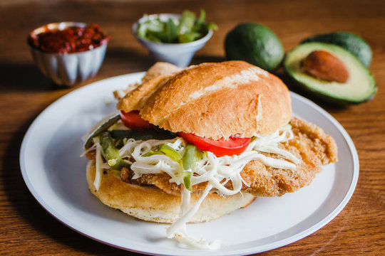 Mexican torta is chicken milanese sandwich with avocado, chili chipotle and oaxaca cheese