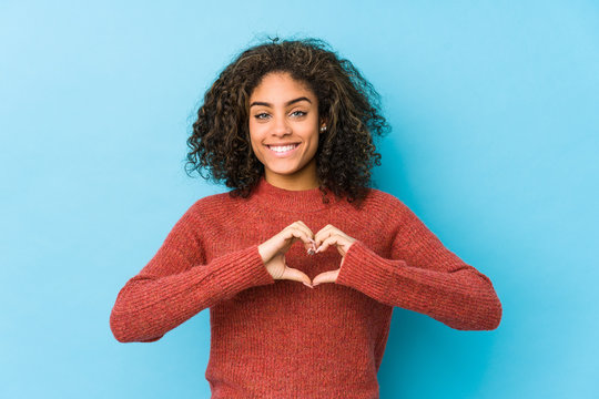 Young african american curly hair woman smiling and showing a heart shape with hands.