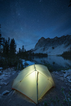 Night sky overt Alice Lake camp Sawtooth Mountains;Backpacking tent illuminated under starry night sky at Alice Lake camp Sawtooth Mountains Idaho, Idaho, United States