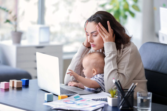 Stressed mother with her baby working in office