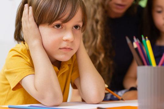 Sad little schoolboy sitting at class