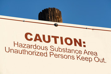 Old caution hazardous substance area unauthorized persons keep out sign.
